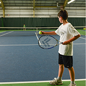boy serving tennis ball